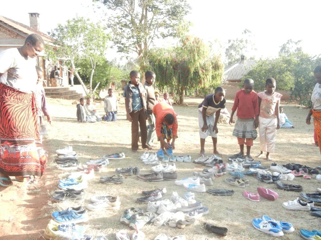 Es ab neue Schuhe im Kinderdorf. Die Dorfchefin Mama Erica hat sie aus der Stadt mitgebracht, und dann haben sich alle daran gemacht passende Schuhe zu finden.